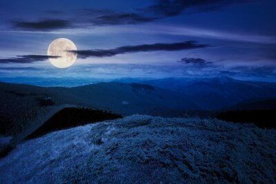hills and valley of mountain landscape at night. clouds on the deep blue sky. beautiful scenery of chornohora ridge in full moon light