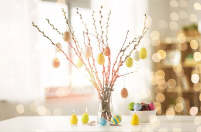 Sticker holidays and object concept - pussy willow branches decorated by easter eggs in vase and candles on table over bokeh lights