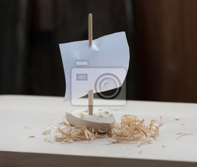 Hölzernes Spielzeugboot mit Segel und Schnitzeln. Draußen