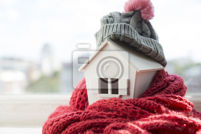 Sticker house in winter - heating system concept and cold snowy weather with model of a house wearing a knitted cap