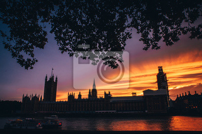 House of parliament and Big Ben in summer evening, colorful orange sky. Symbol of London, Britain, UK