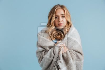 Sticker Image of dissatisfied woman 20s wrapped in blanket looking at camera, isolated over blue background