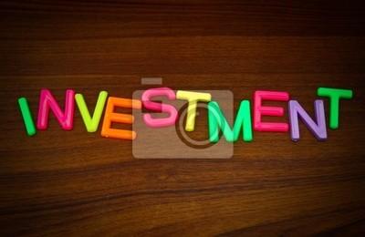 Investitionen in bunten Spielzeug Buchstaben auf Holz Hintergrund