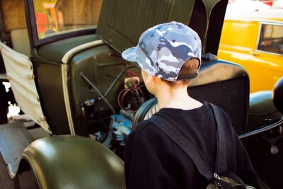 Junge Blick auf Motor der alten militärischen Fahrzeug