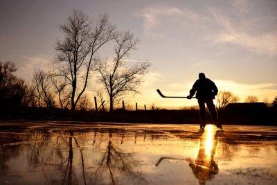 Junge Eishockeyspieler auf Natur-Eis während der Ruhe Winter Sonnenuntergang