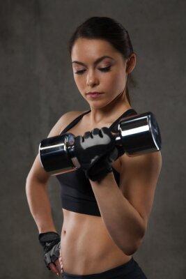Sticker Junge Frau, die Muskeln mit Hanteln in der Turnhalle