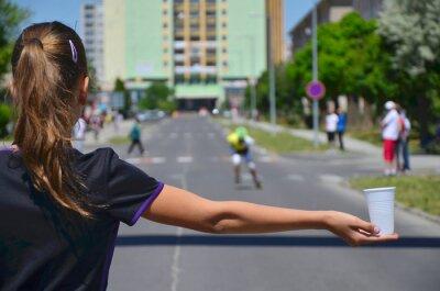 Junge Mädchen halten Tasse Wasser während Rollschuhlauf Wettbewerb und hilft den Athleten zu hydratisieren Sie sich während des Rennens