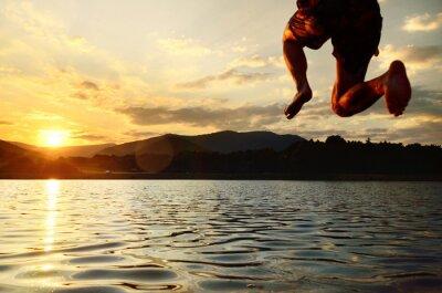 Junger Mann springt in den See bei ruhigen Sommer Sonnenuntergang.