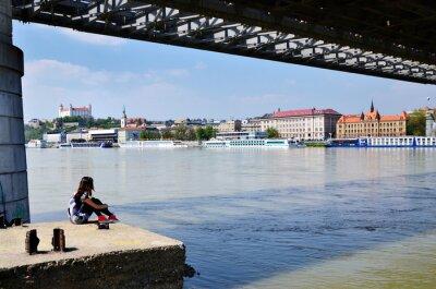 Junges Mädchen, das durch den Fluss in Bratislava unde alte Brücke stillsteht