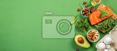 Sticker Keto diet concept - salmon, avocado, eggs, nuts and seeds, bright green background, top view