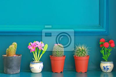 Kleiner Kaktus mit Blume auf der grünen Wand dekoriert