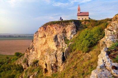 Kleiner Mann auf dem Fahrrad in der Nähe von alten katholischen Kirche in der Slowakei auf Felsen Hügel im Sommer Sonnenuntergang