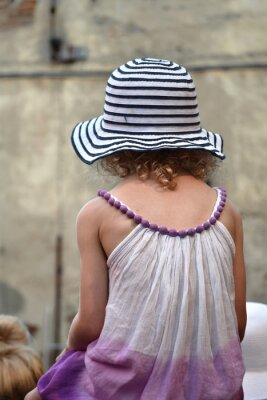 Kleines Mädchen mit Hut mit blauen und weißen Streifen