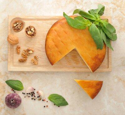 Sticker Kopf von geräuchertem Suluguni Käse auf Holzbrett mit Walnüssen und