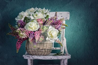 Korb mit Blumen Pfingstrosen und Lupinen