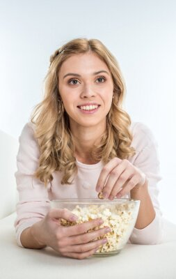 Lächelnde Frau essen Popcorn