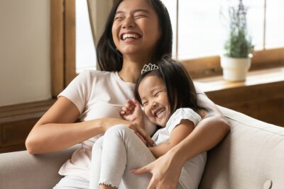 Sticker Lively asian young mother tickling little daughter enjoy free time active weekend together, wearing casual comfortable home clothes kid girl tiara accessory, beautiful happy family having fun concept