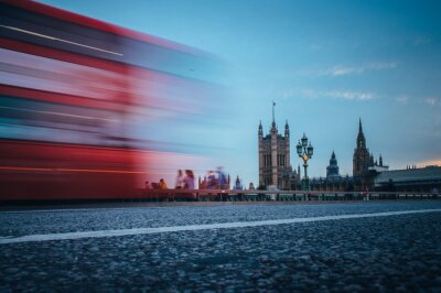 London. Classic red double decker bus crossing Westminster Bridge in front of House of parliament and Big Ben in London