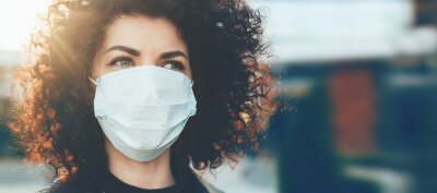 Sticker Lovely curly haired caucasian lady protecting herself from viruses while wearing special mask