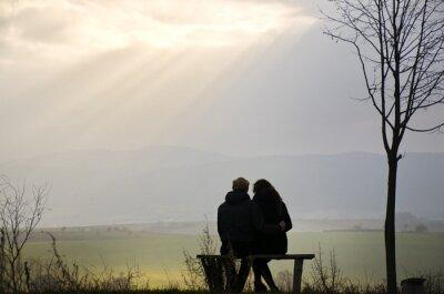 Loving Paar Silhouette auf der Bank über wunderbare Frühling Landschaft mit Herrlichkeit Himmel voller Sonnenstrahlen