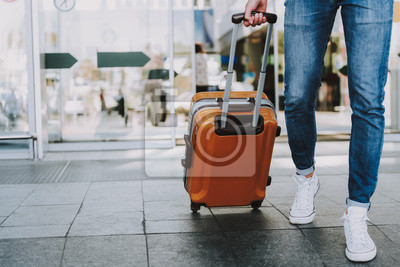 Sticker Male is carrying luggage in hall before trip