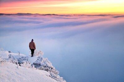 Man steht auf den schneebedeckten Felsen und Blick auf das Tal voller blauer dunkler Wolken und schönen Winter Sonnenaufgang voller lebendiger Farben.