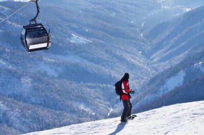 Mann auf Snowboard im sonnigen Winter Aktiv-Tag in den Bergen über Sesselbahn in Bergen Resort