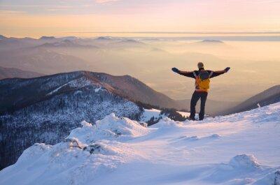 Mann mit offenen Armen über wunderbare Berge Landschaft in Nebel während der Ruhe Winterabend