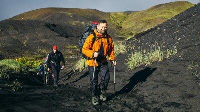Mann Wanderer auf dem Weg in den Inselbergen.  Wanderung im Nationalpark Landmannalaugar, Island.  Tal ist mit Vulkan Asche bedeckt.