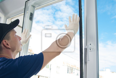 Sticker master in protective gloves, changing a double-glazed window in a plastic window, side view, against the blue sky
