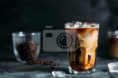 Sticker Milk Being Poured Into Iced Coffee on a dark table