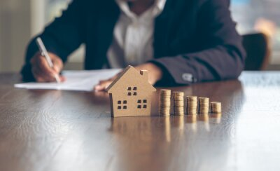 Sticker Modeling wooden houses and coins and dollars placed on wooden tables,preparation concept for house model purchase and the fastest growing real estate economy,moving home or renting property via agent