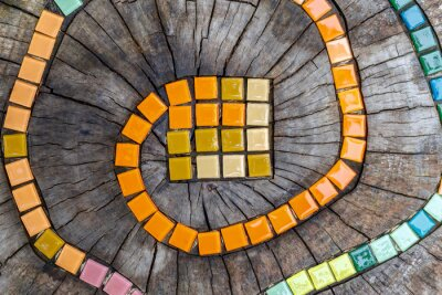 Sticker Mosaic tiles on round cut down tree with cracks stump outside. DIY garden furniture, decorated by hand made element small tiles. Mosaic colorful snake path. Abstract natural wooden background