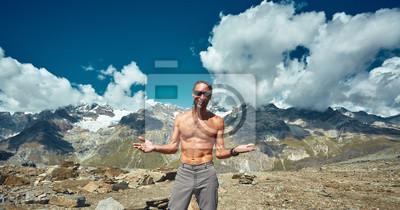 Muskel-Wanderer ohne T-Shirt an der Spitze eines Passes genießen sonnigen Tag in den Alpen auf dem blauen Himmel Hintergrund. Schweiz, Trek bei Matterhorn Berg.