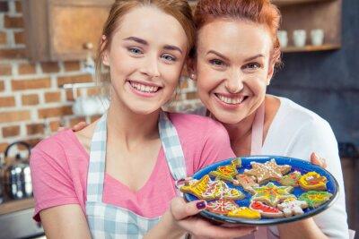 Mutter und Tochter halten Cookies
