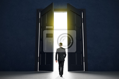 New life beginning concept with businessman entering open black doors in abstract bright space.