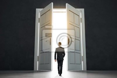 New life beginning concept with businessman entering open white doors in abstract bright space.