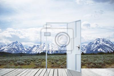 Open door on snowy mountains background