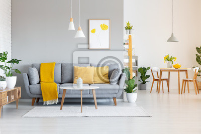 Sticker Orange Decke auf grauem Sofa im modernen Wohnungsinnenraum mit Plakat und Holztisch. Echtes Foto