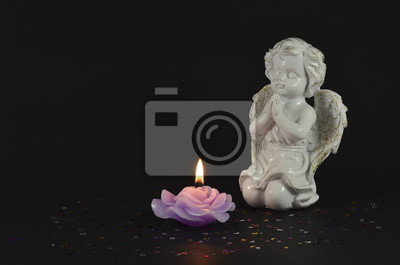 Ornamental angels with candle isolated on black for Christmas
