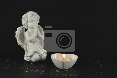 Ornamental angels with heart candle isolated on black