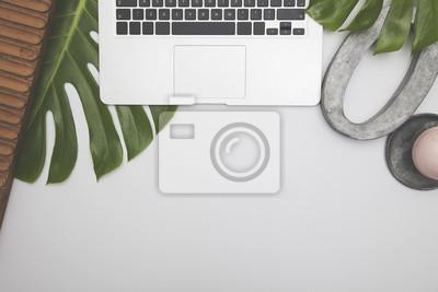 Overhead-Schreibtisch mit Laptop-Computer und grüne tropische Blätter
