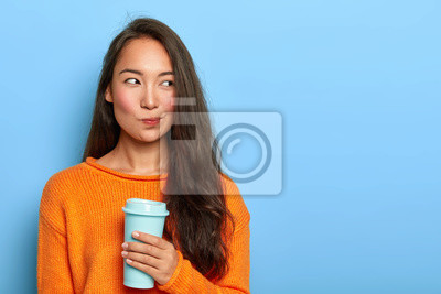 Sticker Photo of pensive brunette woman purses lips, looks thoughtfully aside, holds takeout coffee, makes decision in mind, plans her day, wears orange jumper, stands over blue wall. Asian girl with beverage