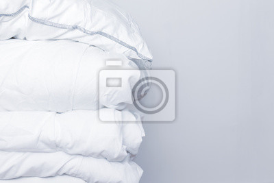 Sticker Pile of white bedding items, pillows and a blanket on white background with copy space