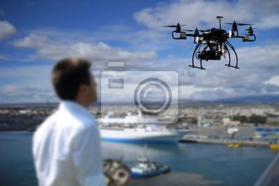 Pilot fliegt die Drohne mit der Kamera mit Küstenhintergrund