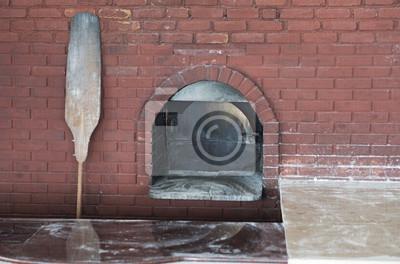 Pizzaofen mit Schaufel auf Hintergrund des roten Backsteins.