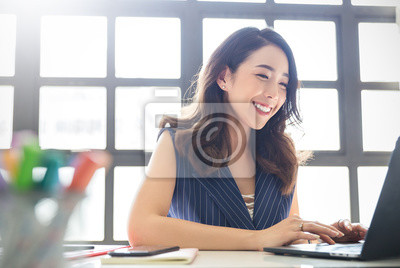 Sticker Portrait of smiling beautiful business asian woman with suit working in office desk using computer with copy space. Business people employee freelance online marketing e-commerce telemarketing concept