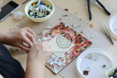 Sticker Process of making a mosaic picture from ceramic tile. The man organizes with a tweezers a puzzle of ceramic elements to build a picture.