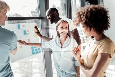 Sticker Professionelle Zusammenarbeit. Positives nettes kreatives Team, das zusammen steht und ihr Projekt beim Arbeiten an ihr bespricht