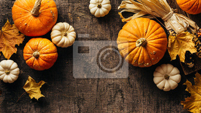 Sticker Pumpkins and corn and autumn leaves on old shabby background. Autumn background with copy space.